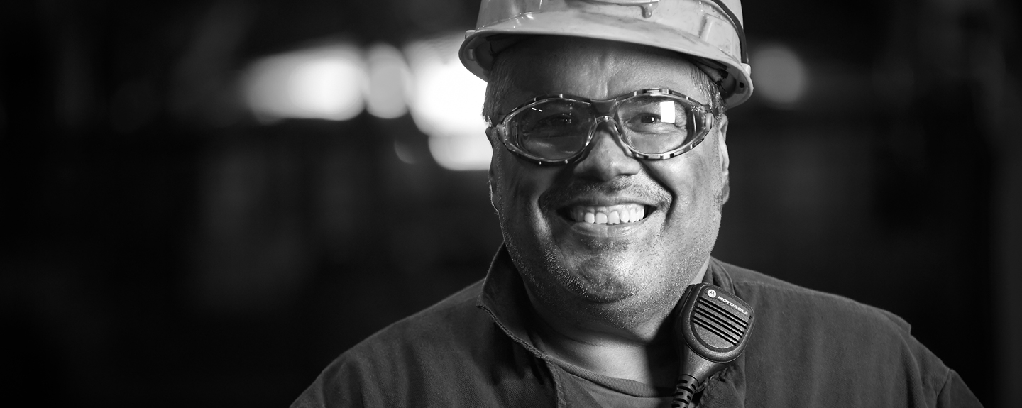 Black and white photo of cast Iron Foundry operator smiling and content